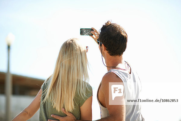 Rear view of couple taking smartphone selfie at Venice Beach  Los Angeles  California  USA
