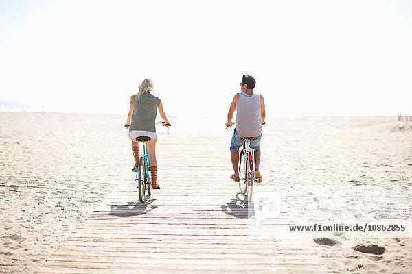 Rückansicht eines radfahrenden Paares an der Strandpromenade von Venice Beach  Los Angeles  Kalifornien  USA