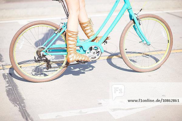 Beine und Riemchensandalen einer jungen Radfahrerin am Venice Beach  Los Angeles  Kalifornien  USA