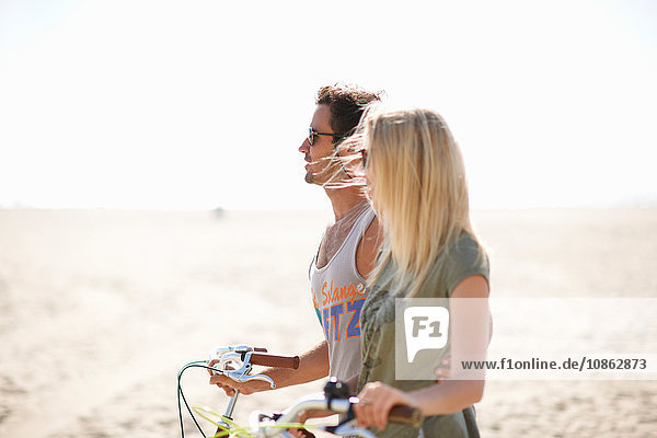 Cycling couple strolling with cycles on Venice Beach  Los Angeles  California  USA