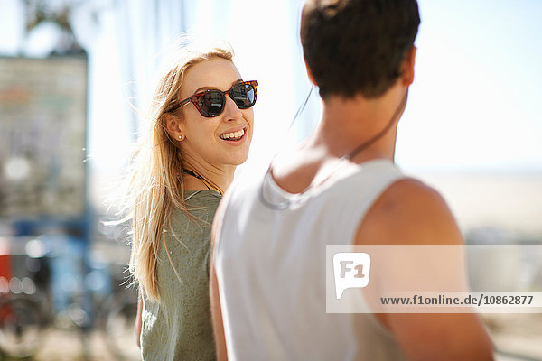 Young woman looking over her shoulder whilst strolling at Venice Beach  Los Angeles  California  USA