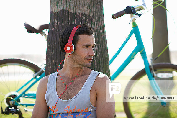Männlicher Radfahrer sitzt am Venice Beach  Los Angeles  Kalifornien  USA  und hört Kopfhörermusik