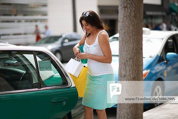 Frau sitzt mit Einkaufstaschen und kämpft darum  in ein Taxi zu gelangen  Los Angeles  Kalifornien  USA