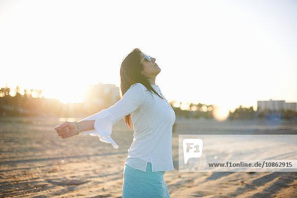 Frau mit offenen Armen am Strand von Santa Monica bei Sonnenuntergang  Cresent City  Kalifornien  USA