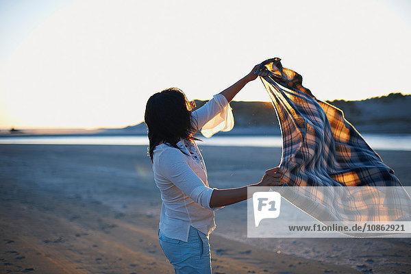 Frau schüttelt bei Sonnenuntergang Decke am Strand  Cannon Beach  Kalifornien  USA