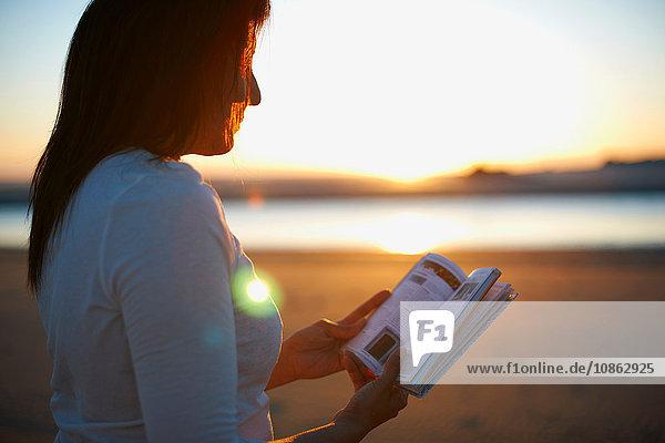 Frau liest Buch am Cannon Beach bei Sonnenuntergang  Kalifornien  USA