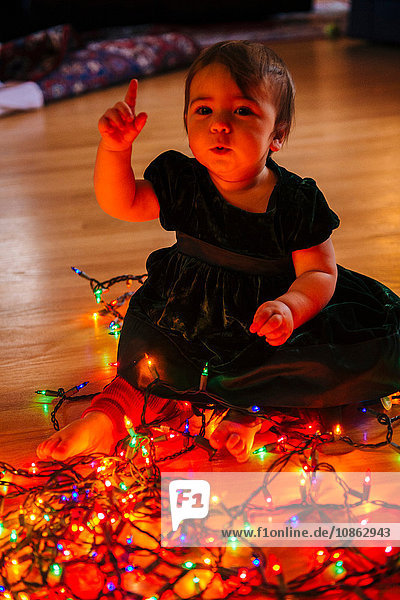 Female toddler raising hand whilst playing with multi-coloured christmas lights on floor