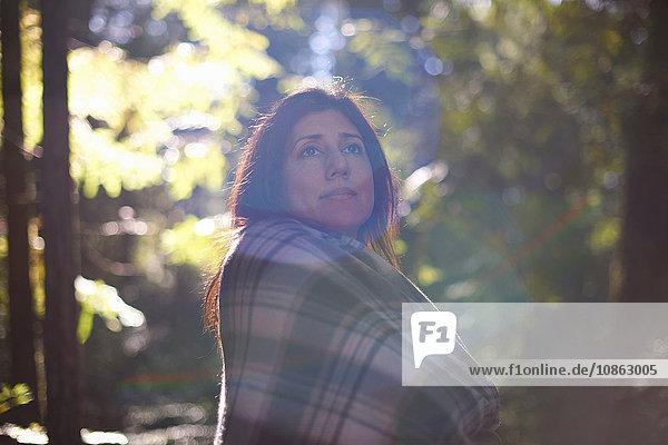 Frau in karierten Schal gehüllt im Wald
