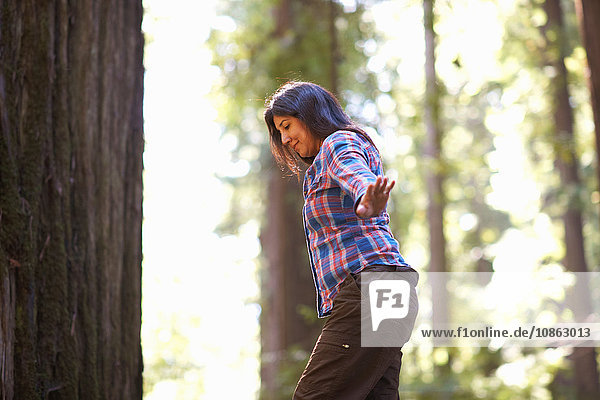 Frau balanciert beim Waldspaziergang