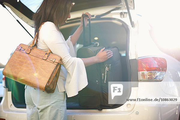 Frau lädt Gepäck in den Kofferraum eines Fahrzeugs