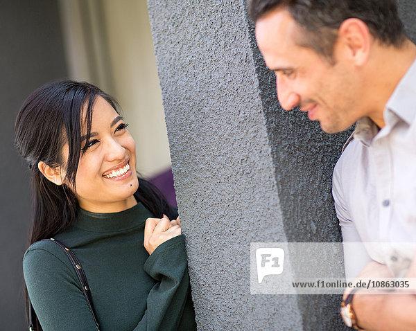An die Säule gelehntes Paar lächelnd von Angesicht zu Angesicht