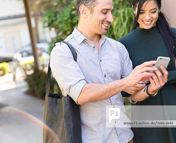 Ein Paar auf der Straße schaut lächelnd auf ein Smartphone