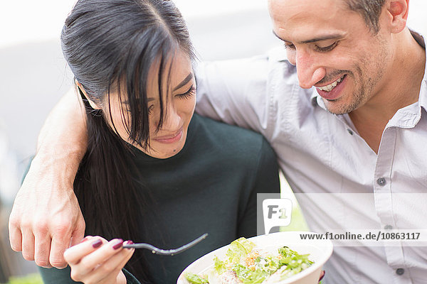 Couple sharing lunch looking down smiling