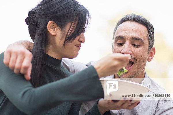 Woman feeding man salad