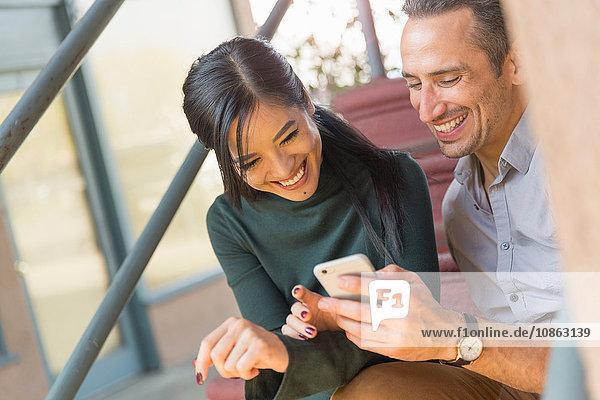 Paar sitzt auf einer Treppe und benutzt ein Smartphone und lächelt