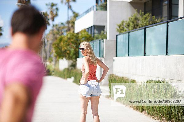 Junge Frau im Freien  Hände auf den Hüften  über die Schulter blickend  lächelnd