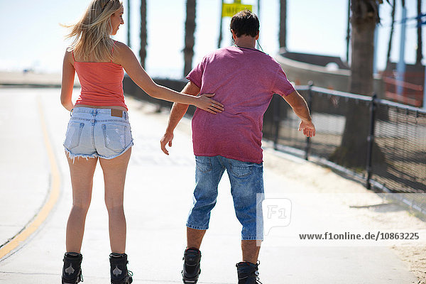 Couple rollerblading outdoors  rear view