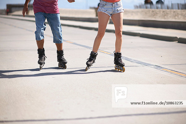 Couple rollerblading outdoors  low section