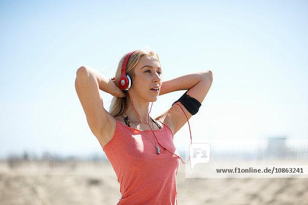 Junge Frau im Freien  mit Kopfhörern und Aktivitäts-Tracker