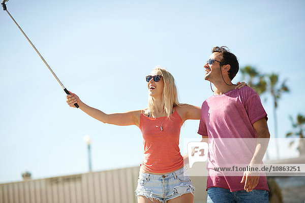 Couple outdoors  taking self portrait  using selfie stick