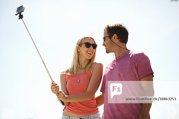 Couple outdoors  woman holding selfie stick