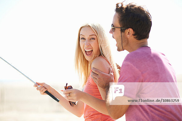 Couple fooling around outdoors  woman holding selfie stick  laughing