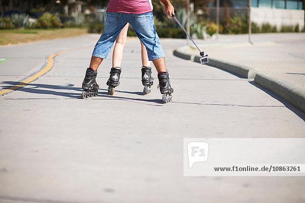 Couple-Rollschuhfahren im Freien  Rückansicht  Niederquerschnitt