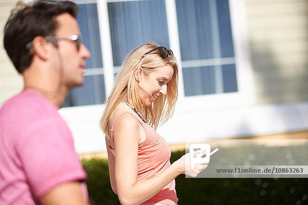 Paar geht im Freien spazieren  Frau schaut auf Smartphone