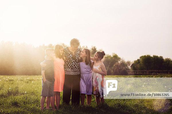 Grandmother in field with grandchildren