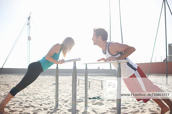 Couple exercising on beach  stretching  using gymnastics parallel bars