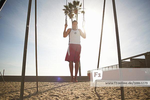 Mittelgroßer Mann  der am Strand trainiert  mit Gymnastikringen