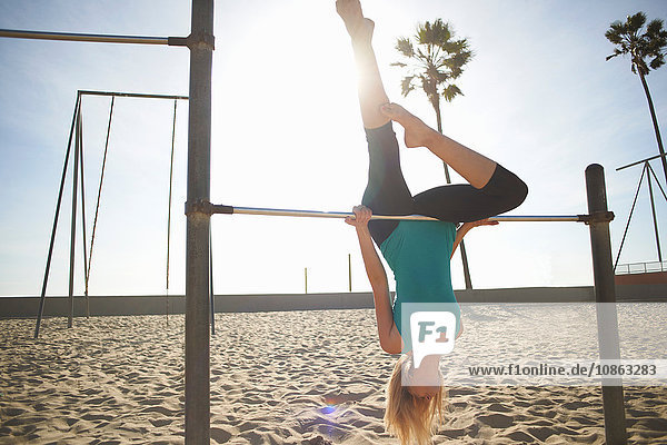Young woman exercising on beach  hanging upside-down on gymnastics training bar