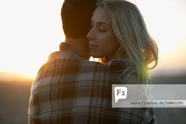 Paar  das sich bei Sonnenuntergang im Freien umarmt  in eine Decke gewickelt