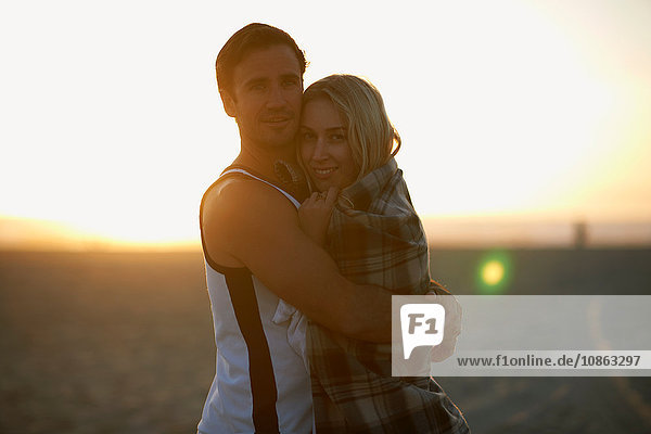 Portrait of couple hugging on beach  at sunset  young woman wrapped in blanket