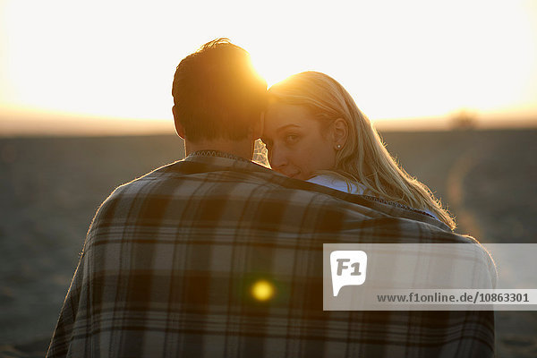 Couple on beach  at sunset  wrapped in blanket  young woman looking over shoulder