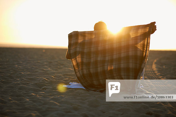 Couple on beach  at sunset  man putting blanket around them
