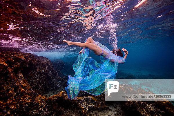 Frau unter Wasser im Ozean über einem Korallenriff