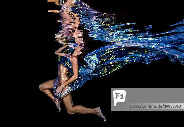Woman underwater in jellyfish fabric