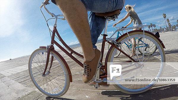 Niedrigwinkelaufnahme eines Radfahrerpaares an der Strandpromenade von Venice Beach  Kalifornien  USA