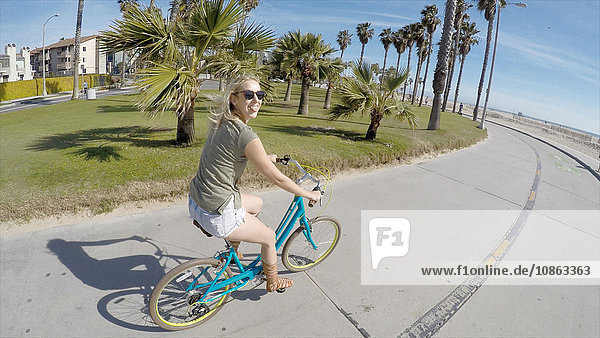 Portrait of young woman cycling at Venice Beach  California  USA
