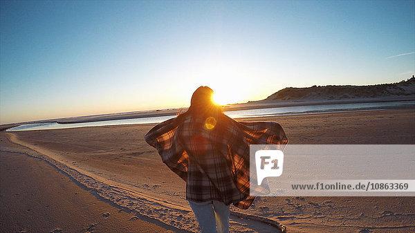 Rückansicht einer Frau mit wehendem Schal  die den Sonnenuntergang von Cannon Beach  Oregon  USA  aus beobachtet