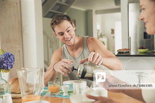 Junges Paar gießt Frühstückskaffee am Küchentisch ein