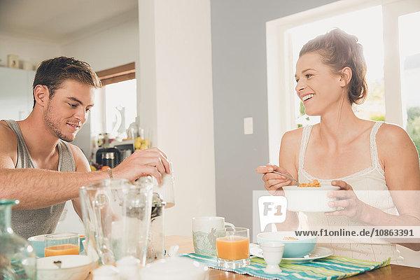 Junges Paar isst Frühstücksflocken am Küchentisch