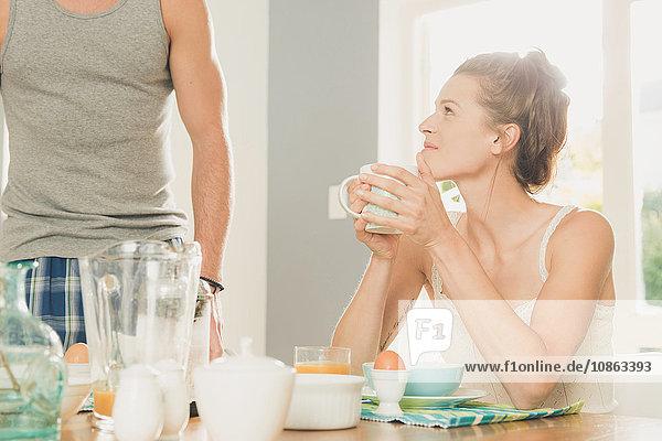 Junge Frau starrt ihren Freund vom Frühstückstisch aus an