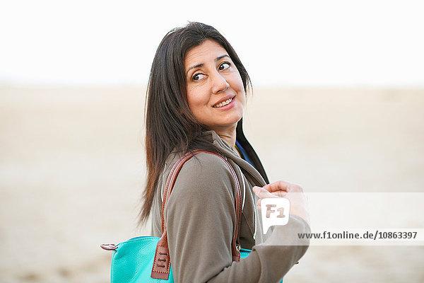 Seitenansicht einer Frau  die eine Handtasche trägt und über die Schulter wegschaut