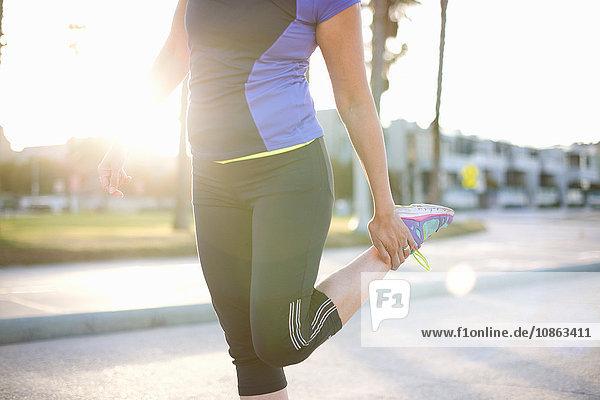 Mittelteil einer Frau in Sportkleidung  die den Knöchel hält und das Bein streckt