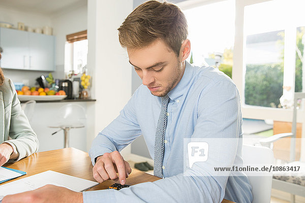 Young couple at kitchen table calculating bills and finance