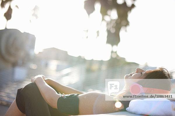 Frau trägt Kopfhörer und Aktivitäts-Tracker und liegt mit geschlossenen Augen