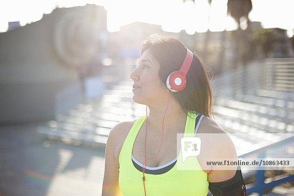 Frau trägt Kopfhörer und Aktivitätsverfolger und schaut weg