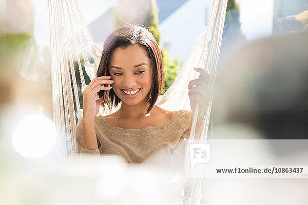 Glückliche junge Frau entspannt sich auf Gartenhängematte